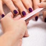 Eine Frau feilt die violett lackierten Nägel einer zweiten Frau