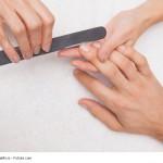 Eine Frau feilt einem Mann einen Fingernagel