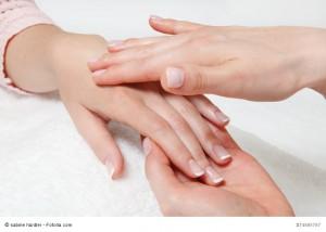 Eine Frau massiert die Hand ener zweiten Frau