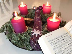 Adventskranz mit 4 brennenden Kerzen neben einem Gesangsbuch